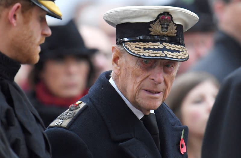 FILE PHOTO: Britain's Prince Harry and Prince Philip attend an event at the Field of Rememberance in front of Westminster Abbey in London