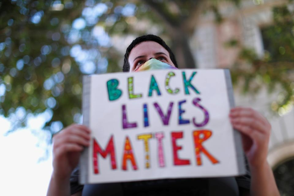 Demonstrator holds a sign during a Black Lives Matter rally protesting the death in Minneapolis police custody of George Floyd and the deaths of Kendrec McDade, Leroy Barnes and JR Thomas by Pasadena police, outside the Pasadena Police Department in Pasadena, California June 4, 2020. (REUTERS/Mario Anzuoni)