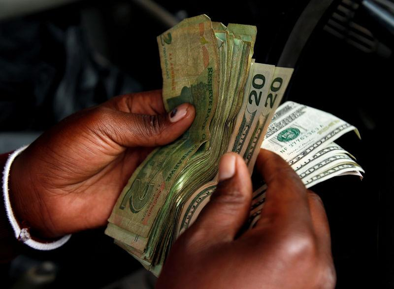 File Photo An Illegal Money Changer Counts Dollar Notes In Harare