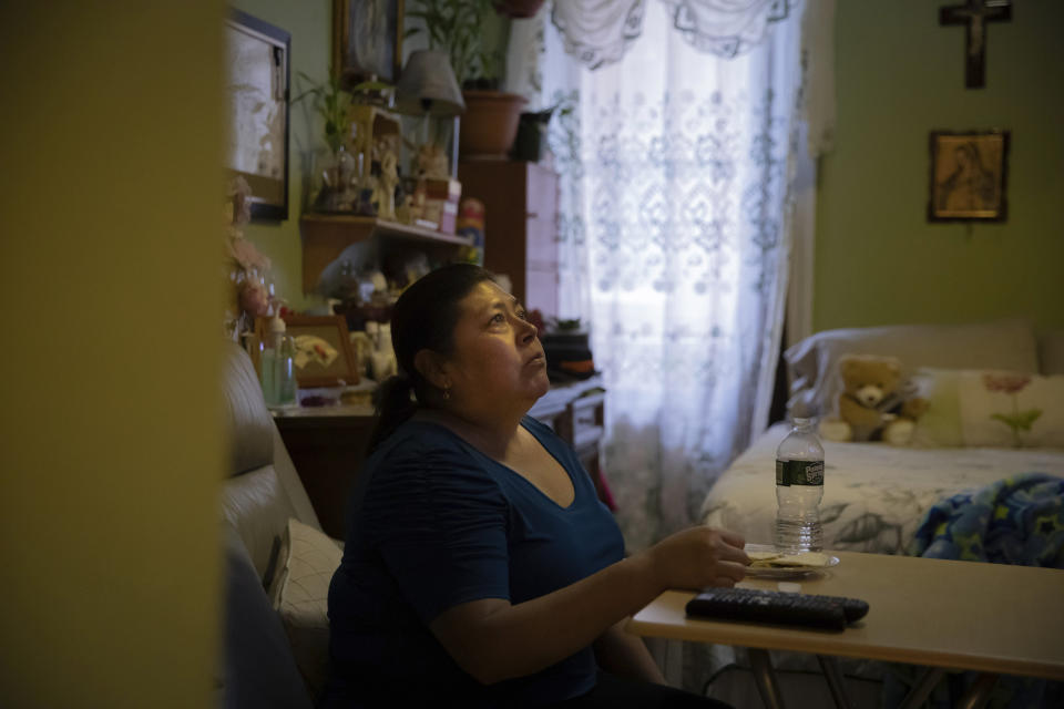 Candida Uraga watches television in the bedroom she rents in New York on Friday, March 19, 2021. She has drained her savings trying to keep up with rent after being laid off from her job as a teaching assistant. (AP Photo/Robert Bumsted)