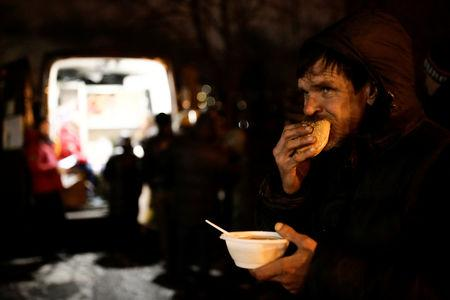 A man eats soup and bread near a van of 'Nochlezhka' charity organization as volunteers distribute meals for homeless people in St. Petersburg, Russia December 5, 2018.  REUTERS/Anton Vaganov