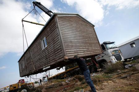 FILE PHOTO: A man helps direct the removal of a pre-fabricated home in the recently evicted illegal Israeli settler outpost of Amona, in the occupied West Bank