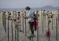 A woman places a rose in the sand on Copacabana beach in honor of 500,000 coronavirus deaths, during a protest against Brazilian President Jair Bolsonaro and his handling of the COVID-19 pandemic, in Rio de Janeiro, Brazil, Sunday, June 20, 2021. Brazil's COVID-19 death toll surpassed the milestone of 500,000 deaths on Saturday night. (AP Photo/Silvia Izquierdo)