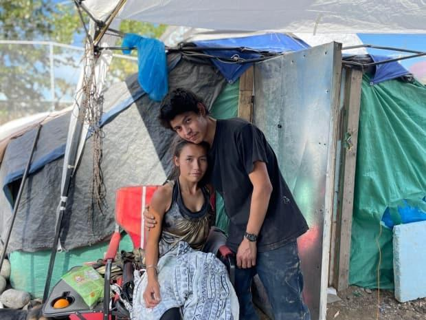 Dallas Caillou and his girlfriend, Kay-lee Hall, pose outside their shelter in a homeless camp in Prince George, B.C. An estimated 50 to 75 people live in the camp and the Prince George Native Friendship Centre says 90 per cent of residents are Indigenous. (Andrew Kurjata/CBC - image credit)