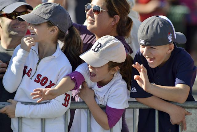 From left, Emma Jadul, 11, sister Caroline Jadul 7, both of Redding, Mass., and Christian Hoyt, 11, of Brockton, Mass., cheer Boston Red Sox players floating by on amphibious duck Bnoats during a rolling victory parade on the Charles River Saturday, Nov. 2, 2013, in Cambridge Mass. (AP Photo/Josh Reynolds)