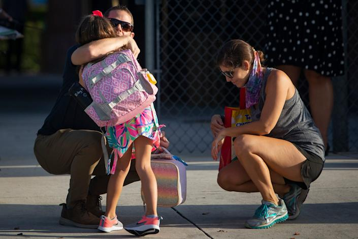 Larry and Lianne Martin hug their daughter Riley as she begins her first day of kindergarten at Lake Park Elementary School in East Naples, Florida, on August 31, 2020.