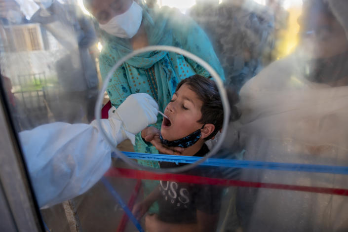 A health worker takes a mouth swab sample of a Kashmiri boy to test for COVID-19 in Srinagar, Indian controlled Kashmir, Saturday, May 8, 2021. Infections have swelled in India since February in a disastrous turn blamed on more contagious variants as well as government decisions to allow massive crowds to gather for religious festivals and political rallies. (AP Photo/ Dar Yasin)