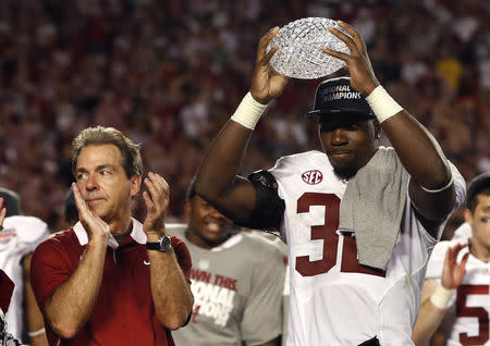 FILE PHOTO: Alabama Crimson Tide linebacker C.J. Mosley holds the trophy as head coach Nick Saban applauds after their team defeated the Notre Dame Fighting Irish in the NCAA BCS National Championship college football game in Miami, Florida, January 7, 2013. REUTERS/Mike Segar
