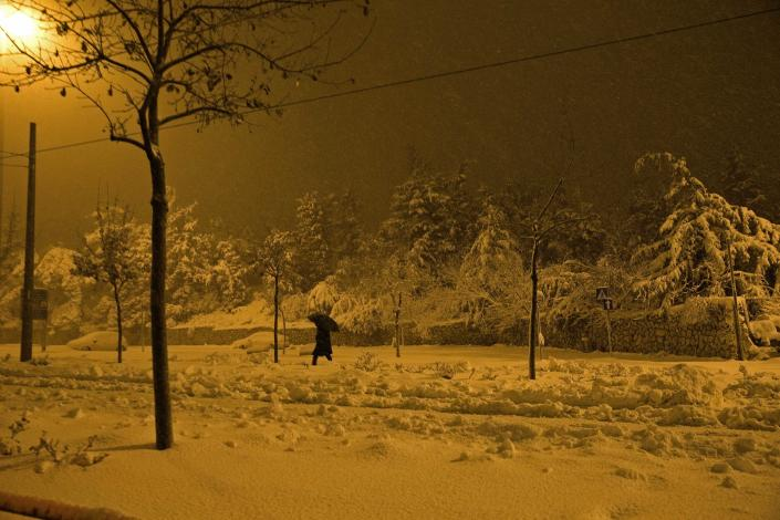 A pedestrian walks on a snow-covered street early morning in Jerusalem February 20, 2015. Snow covered Jerusalem and mountainous areas of Israel early Friday morning and the education ministry closed schools for the day. REUTERS/Ronen Zvulun (JERUSALEM - Tags: ENVIRONMENT SOCIETY)
