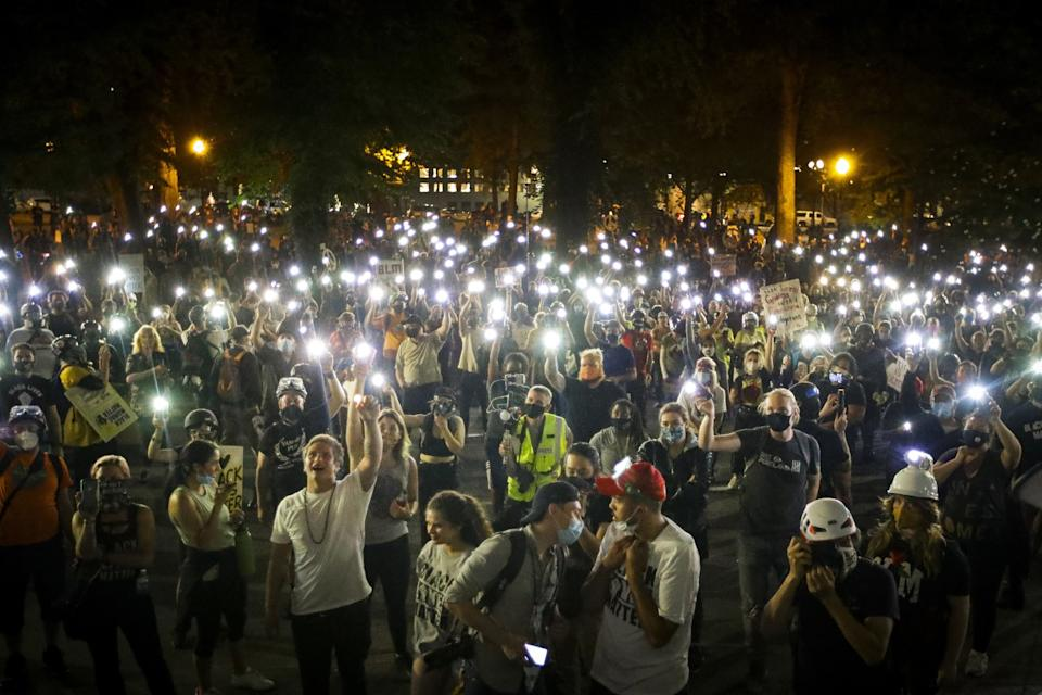 """Demonstrators raise their cellphone lights as they chant and protest in Portland, Ore. <span class=""""copyright"""">(Marcio Jose Sanchez / Associated Press)</span>"""