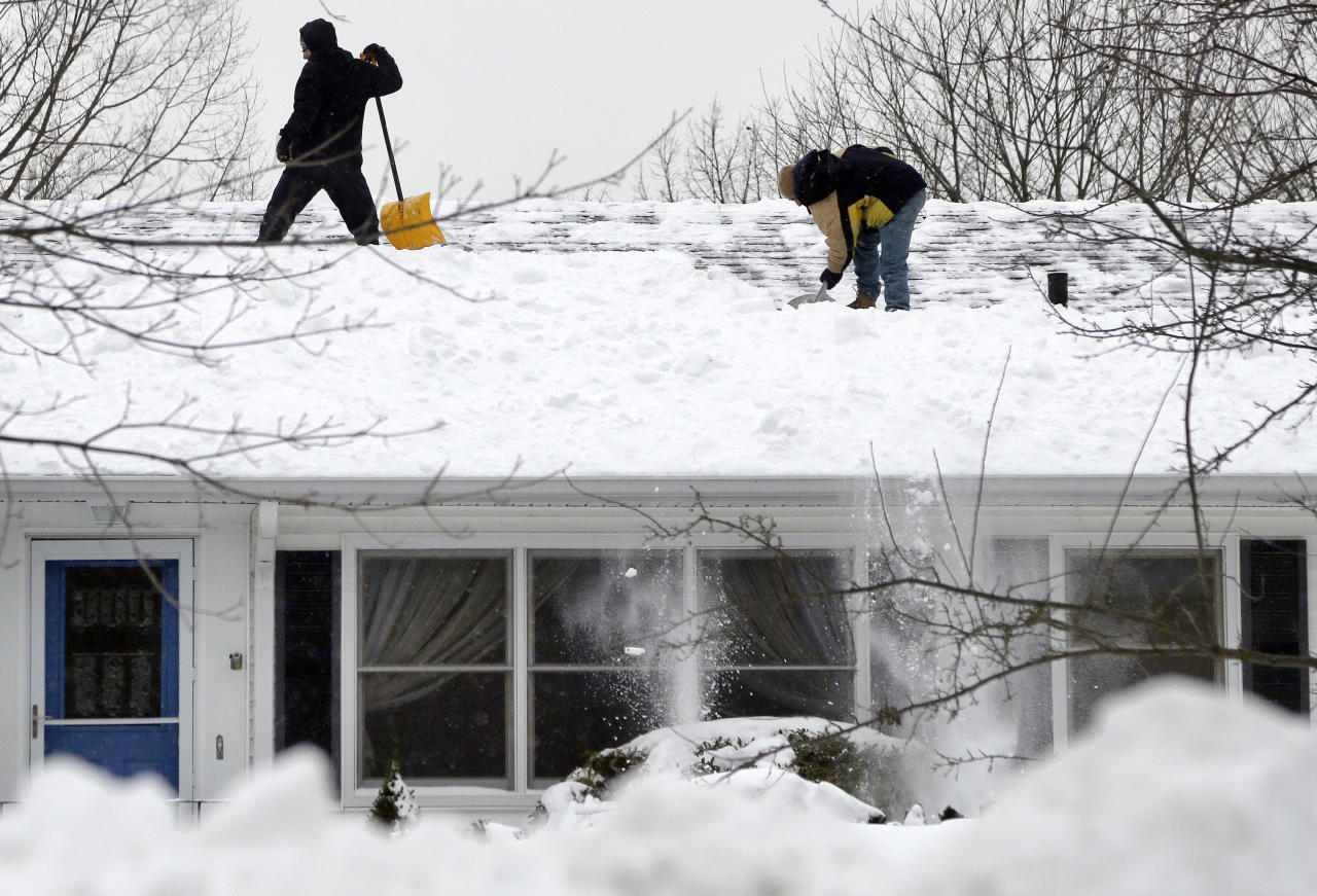 Two men clear snow off a roof of a home in North Andover, Mass. Monday, Feb. 11, 2013. Beleaguered Massachusetts residents returned to work on Monday for the first time since the weekend blizzard, crawling along narrow snow-covered secondary roads and being greeted by a new wintry mix of sleet and freezing rain. (AP Photo/Elise Amendola)