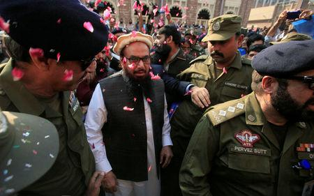 Hafiz Saeed is showered with flower petals as he walks to court before a Pakistani court ordered his release from house arrest in Lahore, Pakistan November 22, 2017. REUTERS/Mohsin Raza