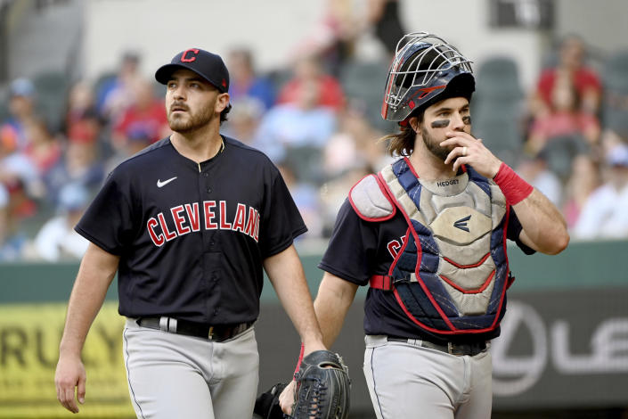 Cleveland Indians starting pitcher Aaron Civale, left, and catcher Austin Hedges walk off the field in the fifth inning during a baseball game against the Texas Rangers in Arlington, Texas, Sunday, Oct. 3, 2021. (AP Photo/Matt Strasen)