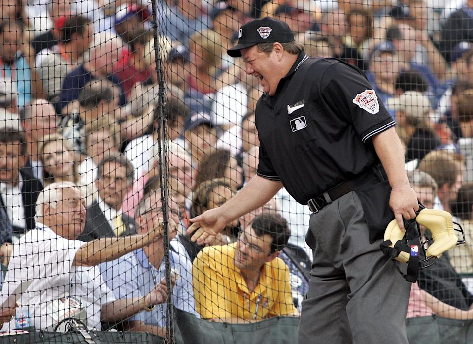 Joe West shakes hands with former Dodgers manager Tommy Lasorda before the start of the All-Star Game in 2005.