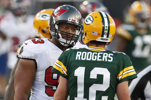 FILE - Tampa Bay Buccaneers defensive end Ndamukong Suh (93) talks with Green Bay Packers quarterback Aaron Rodgers (12) during the second half of an NFL football game in Tampa, Fla., in this Sunday, Oct. 18, 2020, file photo. Rodgers had his worst game of the season in Green Bays 38-10 loss at Tampa Bay Back on Oct. 18, as he threw two game-changing interceptions and completed less than half his pass attempts. Rodgers gets a chance to make amends for that performance Sunday when the top-seeded Packers host the Bucs in the NFC championship game. (AP Photo/Jeff Haynes, File)
