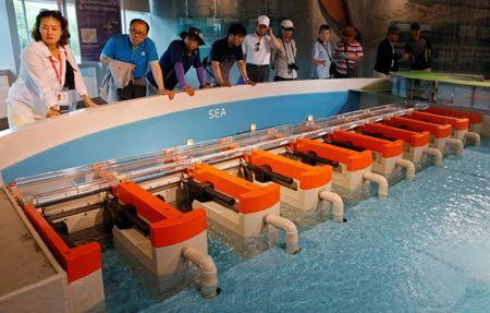 FILE PHOTO: Tourists watch a demonstration of how the Marina Barrage dam works at a gallery in the Marina Barrage facility in Singapore May 29, 2013.  REUTERS/Edgar Su/File Photo