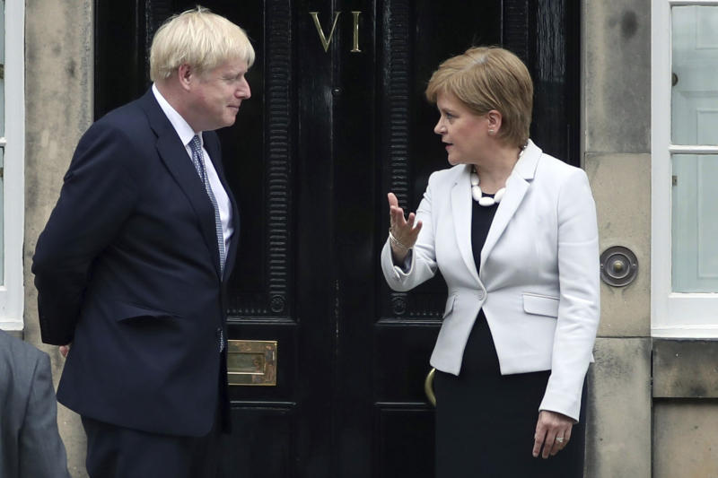 "Scotland's First Minister Nicola Sturgeon, right, gestures to Britain's Prime Minister Boris Johnson, outside Bute House, ahead of their meeting, in Edinburgh, Scotland, Monday July 29, 2019. Johnson made his first official visit as British prime minister to Scotland, pledging to boost ""the ties that bind our United Kingdom"" amid opposition from Scottish leaders to his insistence on pulling Britain out of the European Union with or without a deal. (Jane Barlow/PA via AP)"