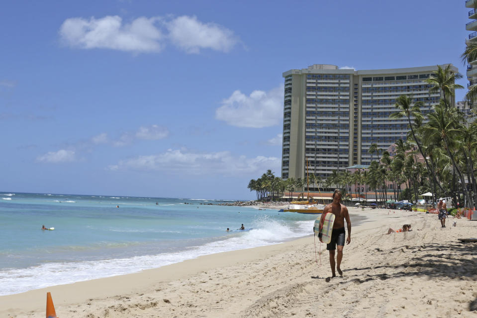 FILE - In this June 5, 2020, file photo, a surfer walks on a sparsely populated Waikiki Beach in Honolulu. Hawaii's governor says that starting Oct. 15, travelers arriving from out of state may bypass a 14-day quarantine requirement if they test negative for COVID-19. (AP Photo/Audrey McAvoy)