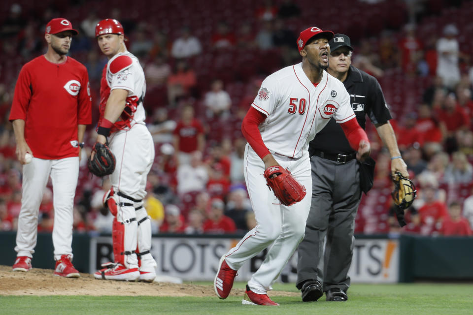 Cincinnati Reds relief pitcher Amir Garrett (50) charges the Pittsburgh Pirates dugout during the ninth inning of a baseball game,Tuesday, July 30, 2019, in Cincinnati. (AP Photo/John Minchillo)