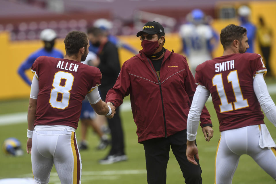 Washington Football Team head coach Ron Rivera shakes hands with Kyle Allen as Alex Smith warms up next to him.