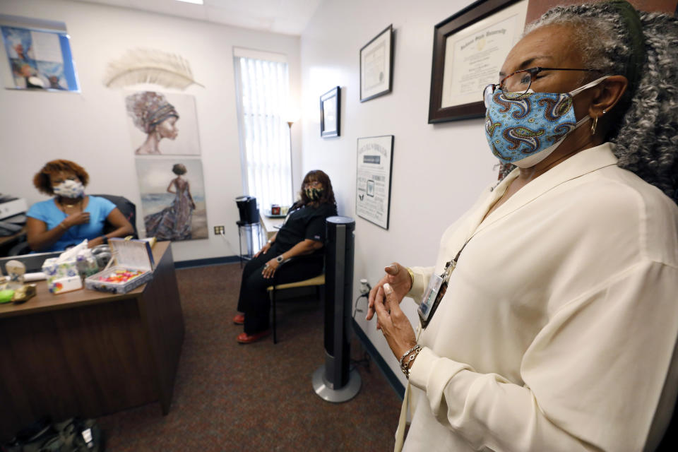 "Clinician and social worker Lisa Williams, right, speaks in front of, Chinnika Crisler, left, and Kim Tate, center, Aug. 14, 2020, at the Community Health Care Center on the campus of Tougaloo College in Tougaloo, Miss. Williams said although the coronavirus pandemic has made a lot of the issues that patients deal with worse, they aren't anything new. ""People have been struggling for a long, long time,"" she said. (AP Photo/Rogelio V. Solis)"
