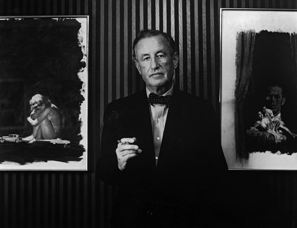 British author and creator of James Bond Ian Fleming (1908-1964) with two pieces of original artwork from the American hardback editions of his books, circa 1960.  (Photo by Horst Tappe/Hulton Archive/Getty Images)