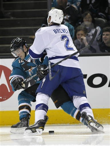 San Jose Sharks left wing Patrick Marleau (12) is checked into the boards by Tampa Bay Lightning defenseman Eric Brewer (2) during the second period of an NHL hockey game in San Jose, Calif., Wednesday, Dec. 21, 2011. (AP Photo/Tony Avelar)