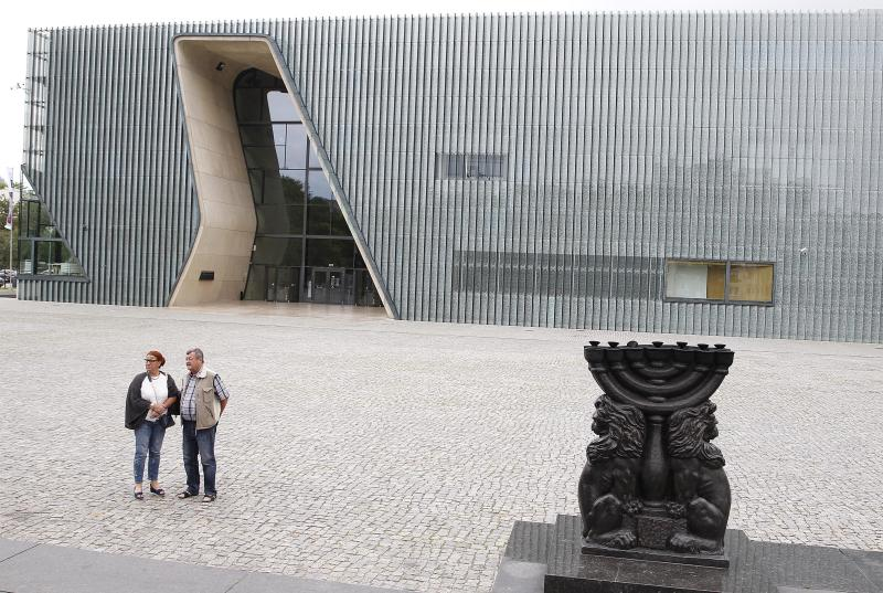 People stand in front of the Museum of the History of Polish Jews 'POLIN' in Warsaw, Poland, Tuesday, 16 July 2019. A Jewish association has said that some private donors to Poland's renowned Jewish history museum have suspended their donations out of concern over the government's failure to extend the term of its director. (AP Photo/Czarek Sokolowski)