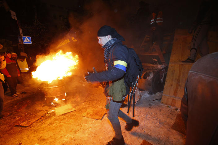 A young man leaves a barricade as riot police try to displace pro-European Union activists from their barricades at the Ukrainian presidential administration building in Kiev, Ukraine, Tuesday, Dec. 10, 2013. Heavily armed riot troops broke into the offices of a top Ukrainian opposition party in Kiev and seized its servers Monday, the party said, as anti-government protests crippled the capital for yet another day. Elsewhere police dismantled or blocked off several small protest tent camps set up near key national government buildings in the city. (AP Photo/Alexander Zemlianichenko)