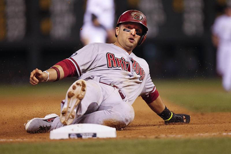 Arizona Diamondbacks' Martin Prado slides into third during the sixth inning of a baseball game against the Colorado Rockies, Friday, Sept. 20, 2013, in Denver. (AP Photo/Barry Gutierrez)