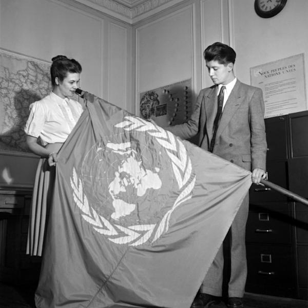 A picture released on August 20, 1948, shows employees of the Paris UN Information Office unfolding the UN flag which was to be hoisted in France for the third General Assembly of the United Nations which adopted the Universal Declaration of Human Rights