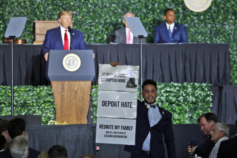 Virginia Del. Ibraheem Samirah, D-Fairfax, yells as he interrupts President Donald Trump's addresses Tuesday, July 30, 2019, in Jamestown, Va., during a commemorative meeting of the Virginia General Assembly at Jamestown Settlement on the 400th anniversary of the meeting of the original House of Burgess. (AP Photo/Steve Helber)