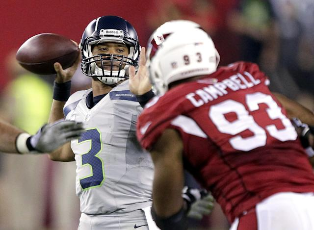 Seattle Seahawks quarterback Russell Wilson (3) throws under pressure from Arizona Cardinals' Calais Campbell (93) during the first half of an NFL football game, Thursday, Oct. 17, 2013, in Glendale, Ariz. (AP Photo/Rick Scuteri)