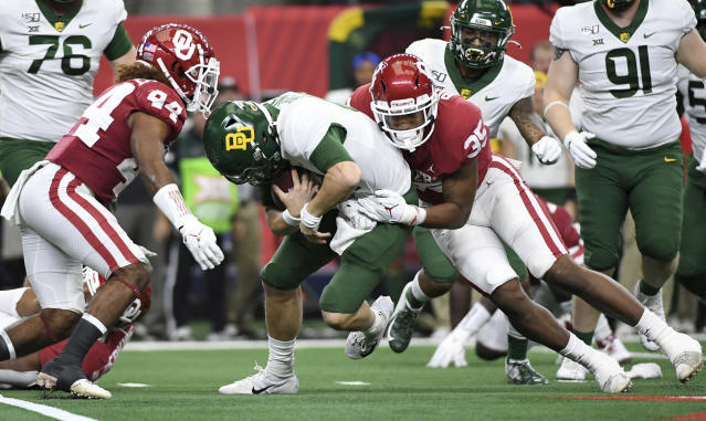 Oklahoma linebacker Nik Bonitto (35) and defensive back Brendan Radley-Hiles (44) sack Baylor quarterback Charlie Brewer during the first half of an NCAA college football game for the Big 12 Conference championship, Saturday, Dec. 7, 2019, in Arlington, Texas. (AP Photo/Jeffrey McWhorter)