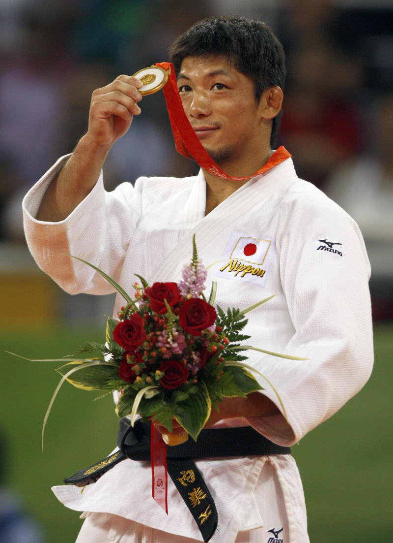 FILE - In this Aug. 10, 2008 file photo, Japan's Masato Uchishiba holds up his gold medal during the judo half lightweight division medal ceremony at the Beijing 2008 Olympics in Beijing. Japanese police said two-time Olympic judo gold medalist Masato Uchishiba has been arrested on suspicion of sexual assault.  (AP Photo/Charles Dharapak, File)