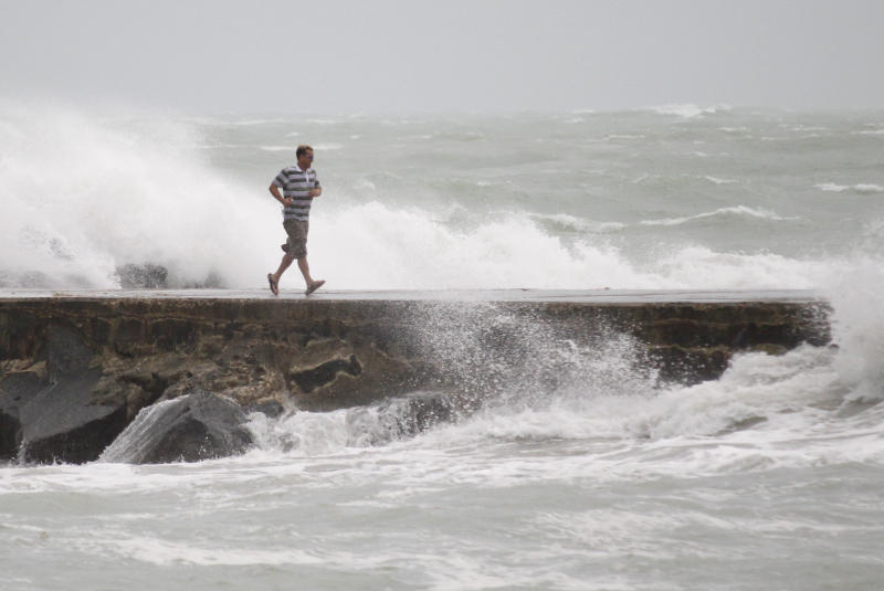 A man runs back from the end of a jetty as waves whipped up by Tropical Storm Isaac crash around him in Bal Harbour, Fla. Forecasters predicted Isaac would intensify into a Category 1 hurricane later Monday or Tuesday with top sustained winds of between 74 and 95 mph. The center of its projected path took Isaac directly toward New Orleans on Wednesday, but hurricane warnings extended across some 330 miles from Morgan City, La., to Destin, Fla. It could become the first hurricane to hit the Gulf Coast since 2008. (AP Photo/Wilfredo Lee)