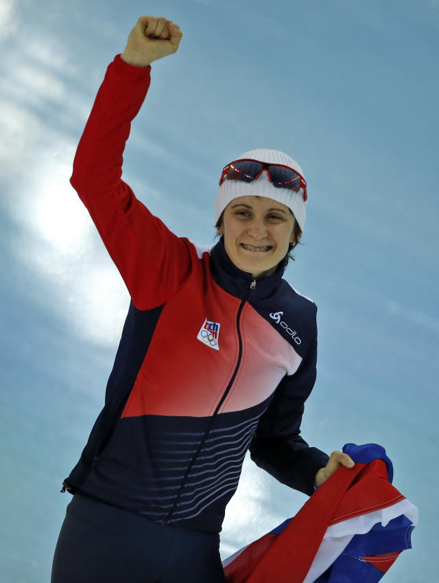 Martina Sablikova of the Czech Republic holds her national flag and celebrates after winning gold in the women's 5,000-meter speedskating race at the Adler Arena Skating Center during the 2014 Winter Olympics in Sochi, Russia, Wednesday, Feb. 19, 2014. (AP Photo/Pavel Golovkin)