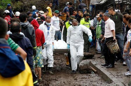Rescue members recover a body in a house after mudslides, caused by heavy rains leading several rivers to overflow, pushing sediment and rocks into buildings and roads, in Manizales, Colombia April 19, 2017. REUTERS/Santiago Osorio