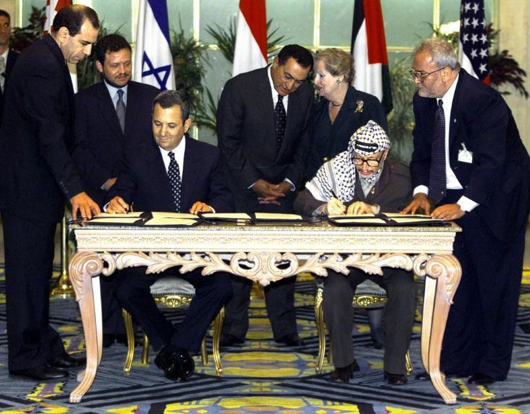 In this photo from September 4, 1999, Israeli Prime Minister Ehud Barak and Palestinian leader Yasser Arafat sign a landmark agreement paving the way for talks on a permanent peace settlement, as senior Palestinian negotiator Saeb Erakat (R) watches