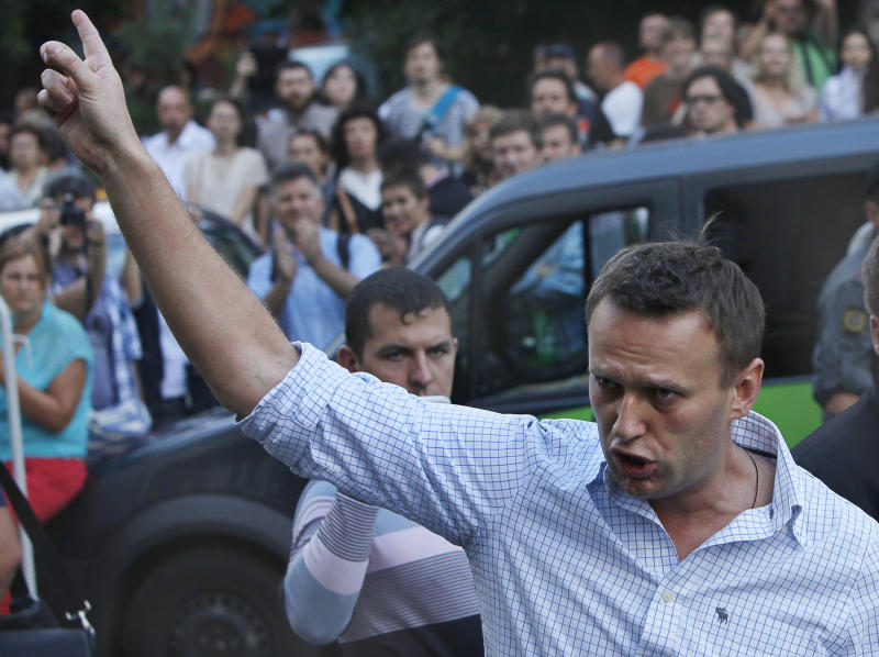 FILE - In this file photo taken on Friday, Aug. 17, 2012, Russian protest leader Alexei Navalny gestures as he walks outside a court in Moscow, Russia. Russian investigators have launched a probe against opposition leader Alexei Navalny, suspecting him of fraud and money laundering.36-year-old Navalny, one of President Vladimir Putin's fiercest critics, was a driving force behind last winter's wave of anti-Putin rallies. Over the winter, the anti-corruption activist spearheaded a series of rallies in Moscow that drew up to 100,000 people to the streets ahead of the March vote that handed Putin a third presidential term.(AP Photo/Alexander Zemlianichenko, File)