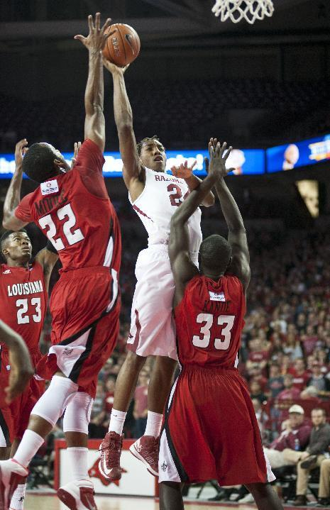 Arkansas' Michael Qualls (24) shoots a basket over Louisiana's Elridge Moore (22) and Vieux Kande (33) in the first half of an NCAA college basketball game in Fayetteville, Ark., Friday, Nov. 15, 2013. (AP Photo/Sarah Bentham)