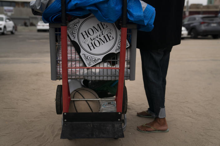 """A homeless woman who goes by Ma Shanti stands next to her cart adorned with a sign that reads """"Home Sweat Home"""" while waiting in line for a free meal in the Venice neighborhood of Los Angeles, Tuesday, June 29, 2021. The proliferation of homeless encampments on Venice Beach has sparked an outcry from residents and created a political spat among Los Angeles leaders. (AP Photo/Jae C. Hong)"""