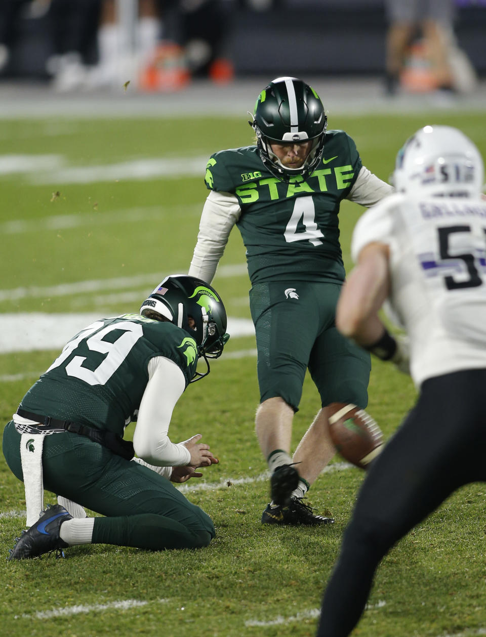 Michigan State's Matt Coghlin (4) kicks a field goal as Bryce Baringer, left, holds during the fourth quarter of an NCAA college football game against Northwestern, Saturday, Nov. 28, 2020, in East Lansing, Mich. (AP Photo/Al Goldis)