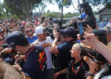 Formula One - F1 - Australian Grand Prix - Melbourne, Australia - 25/03/2017 Mercedes driver Lewis Hamilton of Britain (C) pushes back a TV cameraman in the crush as he signs autographs alongside Red Bull Racing's Australian driver Daniel Ricciardo. REUTERS/Jason Reed