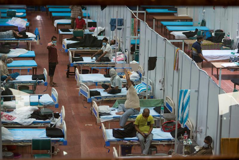 Patients are seen laying in a series of beds placed next to each other.