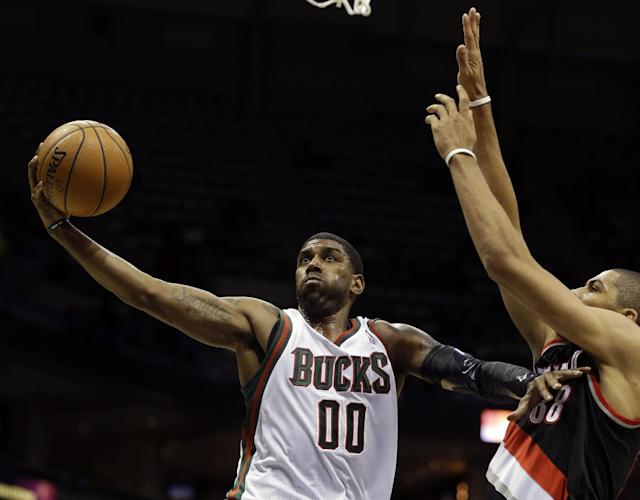 Milwaukee Bucks' O.J. Mayo (00) drives against Portland Trail Blazers' Nicolas Batum, right, during the second half of an NBA basketball game on Wednesday, Nov. 20, 2013, in Milwaukee. (AP Photo/Jeffrey Phelps)