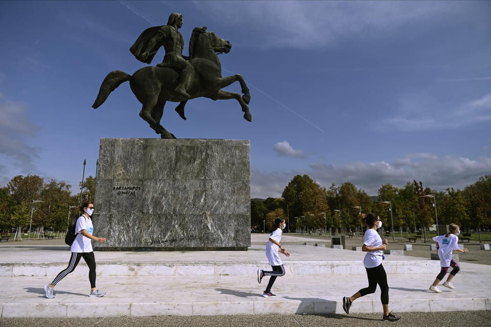 People participate in an event, organized by the local medical association, to support the use of protective masks, in front of a statue of Alexander the Great, in the northern city of Thessaloniki, Greece, Saturday, Oct. 3, 2020. Lung doctors staged a public demonstration of the benefits of face masks by fast-walking a distance of 2 kilometers (1.25 miles) through the city center aiming to debunk a widely-circulated rumor by anti-mask conspiracy theorists that wearing one left people short of breath. (AP Photo/Giannis Papanikos)