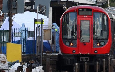 <span>Forensic investigators search on the platform at Parsons Green Tube station on Friday afternoon</span> <span>Credit: HANNAH MCKAY /REUTERS </span>
