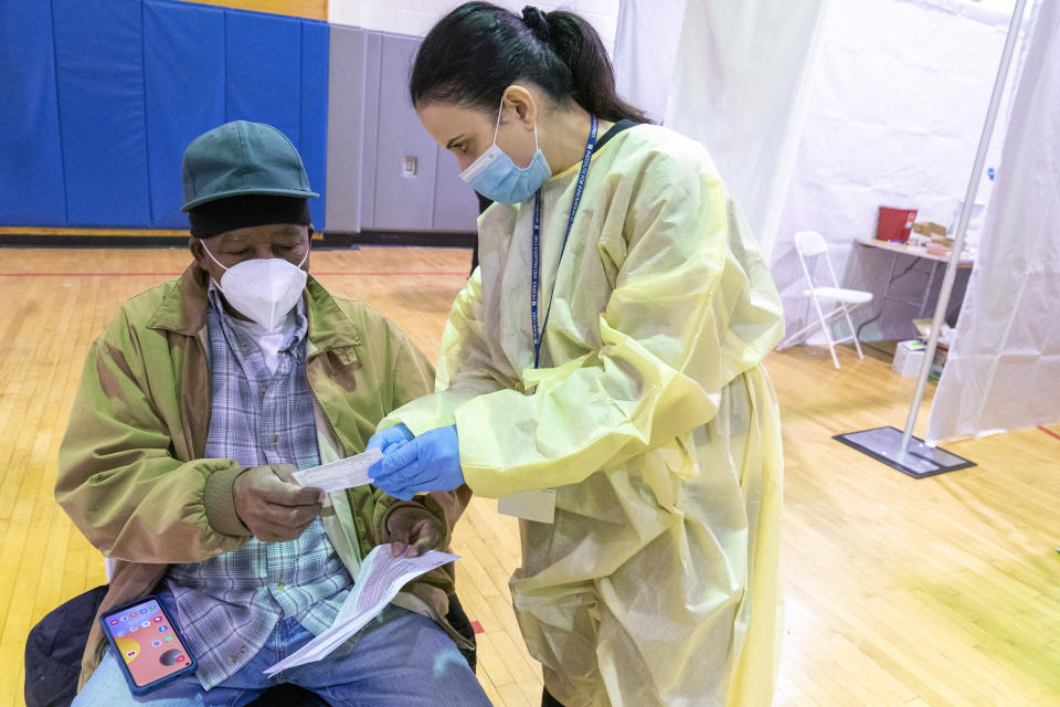 Registered Nurse Rita Alba points out to Beltran Orlando the return date on his vaccination card while he rests in the recovery area after his receiving the first dose of coronavirus vaccine at a pop-up COVID-19 vaccination site at the Bronx River Addition NYCHA complex, Sunday, Jan. 31, 2021, in the Bronx borough of New York. From elderly Cuban Americans in Florida to farmworkers in California, Latinos face daunting barriers like fear, language and a lack of education and access as the COVID-19 vaccines roll out, creating risks for public health as the virus mutates and spreads. (AP Photo/Mary Altaffer)