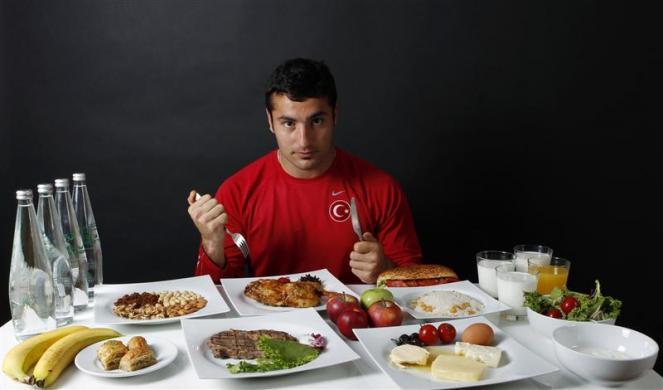 Turkish javelin thrower and Olympic hopeful Fatih Avan, 23, poses in front of his daily meal intake in Ankara May 29, 2012.
